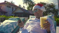 Man in Santa Claus Hat by Pool. Celebrating New Year and Christmas in Hot Stock Footage