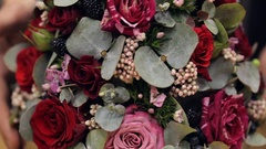 Bouquet of red and pink roses, blackberries, small blossoms and green leaves Stock Footage