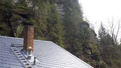 Brick chimney on cabin roof in lush green forest Stock Footage