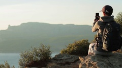 Young woman taking a self-portrait with her smartphone in the mountains HD Stock Footage