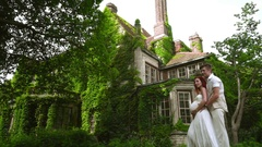 Pregnant couple hugging near country house. Love couple near old house. Stock Footage