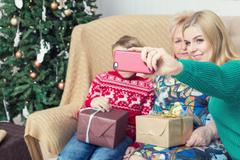 Happy family taking picture with smartphone on Chistmas decorations Stock Photos