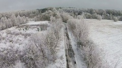 Aerial view of winter forest with road and snow on the trees Stock Footage