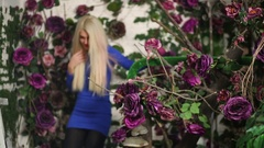 Blonde woman in blue dress going down stairs among artificial flowers. Stock Footage