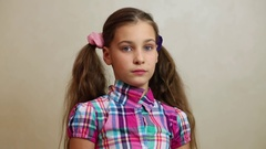 Girl in checkered shirt with two bunches smiling and turning head. Stock Footage