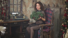 Woman in transparent dress sitting in old chair with spruce branch Stock Footage