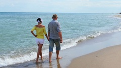 4K. Adult couple  go on  seashore, coastline in summer time Stock Footage