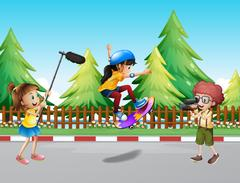 Kids shooting vdo of girl skateboarding in the park Piirros