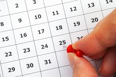 Person hand putting pin on number 25 in calendar Stock Photos