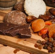 Chocolate, dried apricots, and homemade cookies on a wooden board Stock Photos