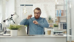 Bearded Tech Guy Starts Dancing While Sitting at His Desk in  Bright Office. Stock Footage