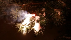 Sparkler stick burn in night, bright flash and flakes illuminate pine needles Stock Footage