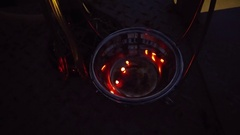 Tweezers near sparking coals in vase close up in twilight Stock Footage