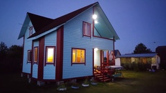 White country house with light in windows on yard in twilight Stock Footage