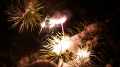 Bright sparks from small bengal light stick in snow at pine branch Stock Footage