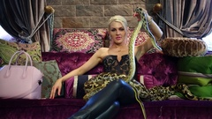 Blonde woman holding in hand small snake and big snake lying on her legs Stock Footage