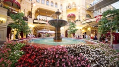 Fountain with flowers around and people near in GUM on Red Square Stock Footage