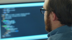 Close-up of a Man's Head in the Background Computer Screen with Code Line. Stock Footage
