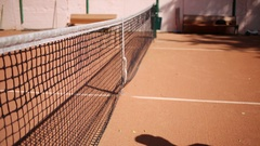 Legs and hands of man beating tennis ball by racket on court at sunny day. Stock Footage