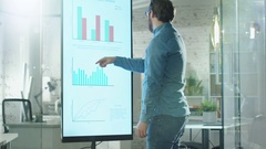 Young Man Works with Charts on His Electronic Whiteboard.  Stock Footage