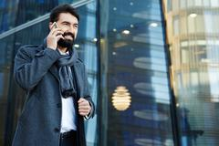 Contemporary business leader speaking on cellphone outdoors Stock Photos