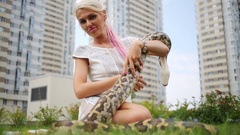 Woman sitting with snake in hands on grass near highrise houses Stock Footage