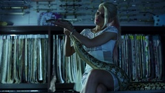 Woman sitting in dark with spotty snake on her legs and stroke it in shop. Stock Footage