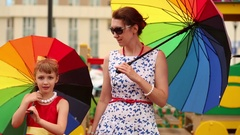 Mother and daughter standing near and turning multi-color umbrellas Stock Footage
