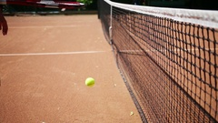Lower part of body of man coming to tennis net beating ball with rocket Stock Footage
