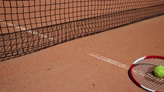 One yellow balls under tennis racket lying near on ground of court. Stock Footage
