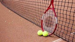 Two yellow balls and tennis racket leaning on tennis net on court Stock Footage
