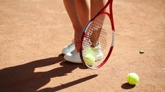 Legs of woman getting up tennis ball with racket and her shoe on court Stock Footage