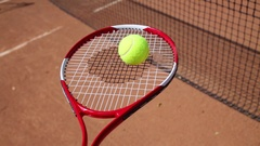 Hand holding and moving tennis racket with yellow ball on it on court Stock Footage