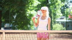Beautiful woman with tennis racket leaving and coming to net on court Stock Footage