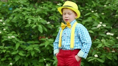 Boy in hat, bow-tie and red trousers turning hands in pockets and touching hat Stock Footage