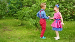 Small boy and girl dancing holding hands and twitching legs Stock Footage