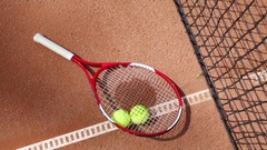Tennis racket and two balls lying near tennis net on ground of court Stock Footage