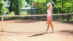 Blonde woman with tennis racket going along net and beating ball Stock Footage