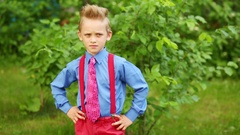 Boy in blue shirt, tie and red trousers with suspenders standing hands on hips Stock Footage