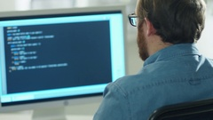 Shot From Behind of a Bearded Young Developer Writing Code on His Computer. Stock Footage