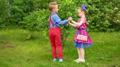 Small boy and girl dancing holding hands and turning femor near bushes. Stock Footage