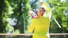 Large woman with tennis racket in hand doing selfie on court at sunny day. Stock Footage