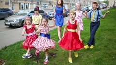 Seven girls and boys in multi-color clothes dancing and twitching legs Stock Footage