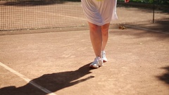 Legs of large woman beating tennis racket on ball near net on court Stock Footage