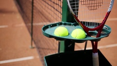 Tennis racket and two yellow balls near tennis net close up. Stock Footage