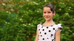 Girl in spotted white dress and hairdo in gel, turning and smiling Stock Footage