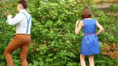 Pair of boy and girl in blue dress dancing near green bushes and house. Stock Footage