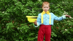 Boy in red trousers and bow tie putting on hat in hand and taking it off Stock Footage