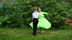 Boy with number on back and girl in dress beautifully dancing partner dance Stock Footage
