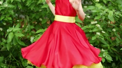 Red with yellow dress on girl turning to sides near bushes close up. Stock Footage
